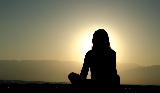 women-meditating-at-sunset